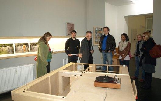 Robert Krokowski und Jofroi Amaral mit Besucherinnen und Besuchern am Modell Lage 3zu20